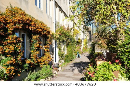 Old Terraced Cottages and a Beautiful Leafy Walkway in Rural England - stock photo