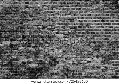 Old textured black and white rough brick wall