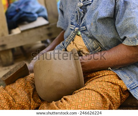 Old Thai female hand shaping a pot from gray color clay - stock photo