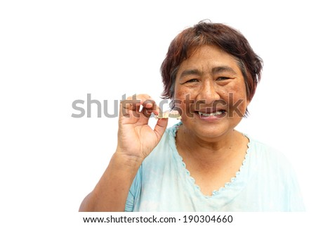 Old thai woman smile and hold denture. And blank area at left side - stock photo