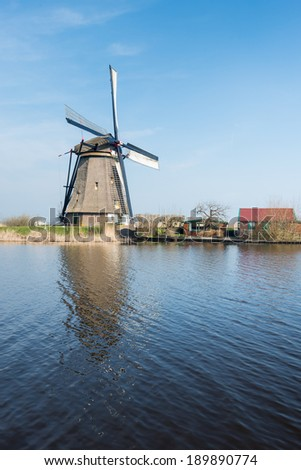 Old thatched polder mill near the Dutch village of Kinderdijk on a sunny spring day. - stock photo