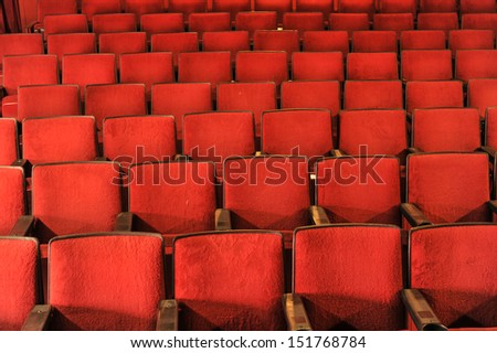 Old theater with rows of red seats with wooden arm rests - stock photo