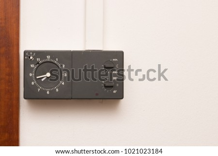 old thermostat with clock at home