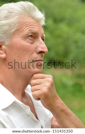 Old thoughtful man out for a walk in the park in summer - stock photo
