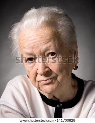 Old  thoughtful woman on a gray background