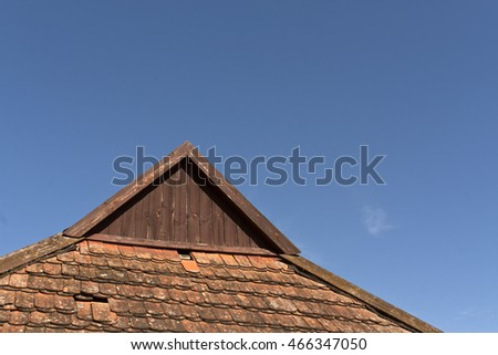 Old tile roof against blue sky. architectural background.