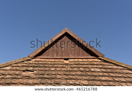 old tile roof top against blue sky. Architectural background and texture for design.