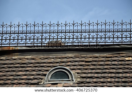 Old tiled roof with small oval window and ornamental iron construction on top - stock photo