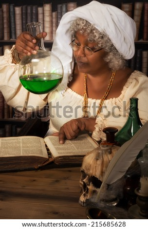 Old time alchemist working in her laboratory with green poison in a flask - stock photo