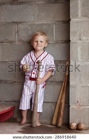 Old time baseball.  Adorable little boy dressed in a vintage uniform and standing in a dugout with baseballs and bats. - stock photo