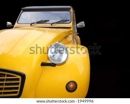 Old timer yellow car isolated on black background