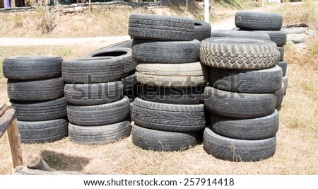 Old tire heap in sunlight - stock photo