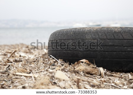 Old tire washed up on shore with other flotsam in France. - stock photo
