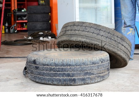 Old tires.Old used car tires in secondary car parts shop garage.Used car tires pile in the tire repair shop yard.Column stack of old used car tires in secondary car parts shop garage. - stock photo