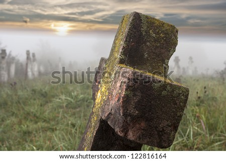 Old tombstone in down in old cemetery - stock photo