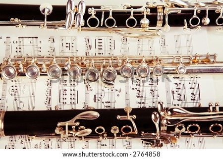 Old tone clarinet and flute over sheet music - stock photo