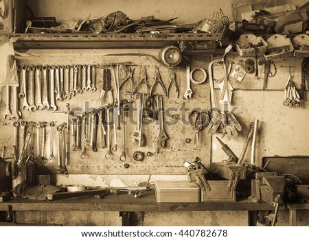 Old tools hanging on wall in workshop , Tool shelf against a wall vintage style - stock photo