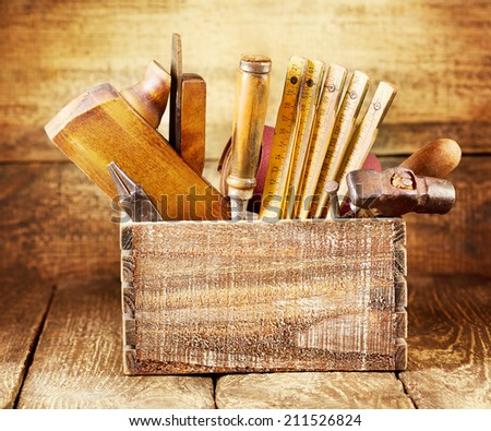old tools in a box on wooden background - stock photo
