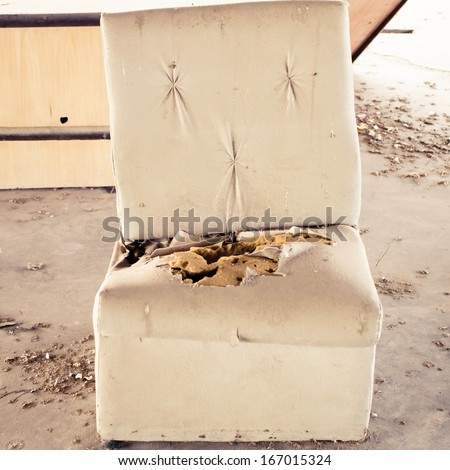 Old torn and dirty sofa in old house. - stock photo
