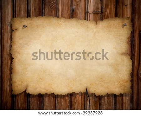 old torn paper pinned by nails to grunge wooden wall - stock photo