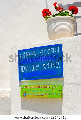 Old touristic signpost on a white wall in Sifnos island Greece - stock photo