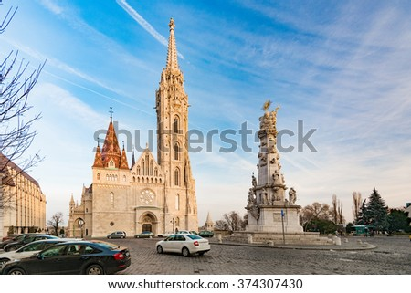 Old town architecture of Budapest. Buda temple church of Matthias. Buda's Castle District. Blue cloudy sky in background and parked cars in foreground. Hungary, Europe.