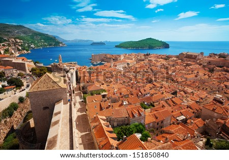 Old town of Dubrovnik with Lokrum island on background with red roofs - stock photo