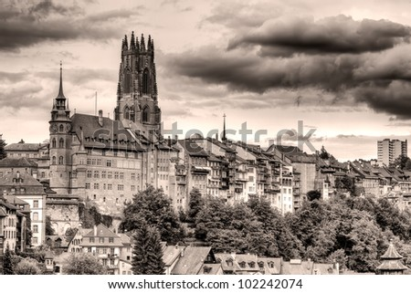 old town of Fribourg, Switzerland with cathedral  St.Nicholas Cathedral and 74 m high bell tower vintage black and white look - stock photo