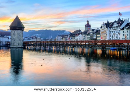 Old town of Lucerne reflecting in the water of Reuss river on sunset, Lucerne, Switzerland - stock photo
