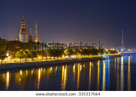 Old Town of Riga and River Daugava at night, Riga Cathedral and Saint Peter church, Railway Bridge and Riga Radio and TV Tower in the background, Latvia - stock photo