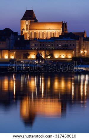 Old Town of Torun in Poland, reflection on Vistula River waters, illuminated Cathedral Basilica of St. John the Baptist and St. John the Evangelist and city walls. - stock photo