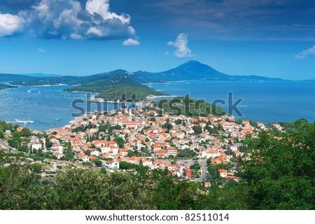 Old town on Adriatic island under blue sky. Mali Losinj, Croatia, popular touristic destination. - stock photo