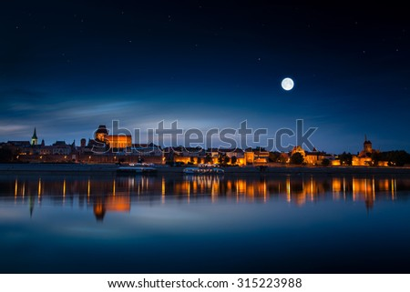 Old town reflected in river at sunset. Torun, Poland. - stock photo