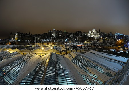 Old Town skyline, over the roof of Waverley railway station, Edinburgh, Scotland, UK, at night in winter with snow - stock photo