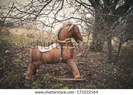 Old toy horse under old tree in autumn time - stock photo