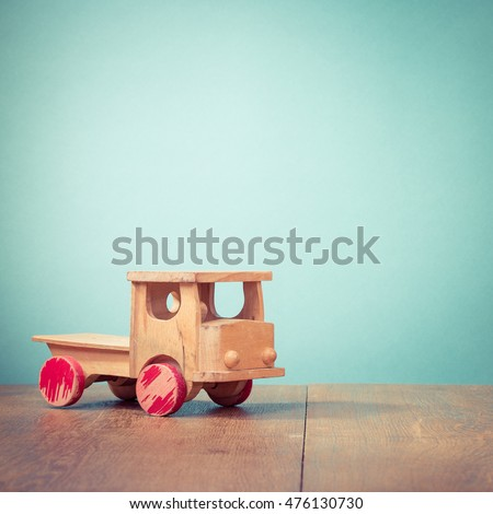 Old toy wooden truck front aquamarine background. Retro style filtered photo