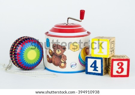 Old toys yo-yo, tin hurdy-gurdy musical box and cubes with numbers, isolated - stock photo