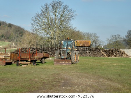 Old Tractor and rusty Trailer parked in a farmyard in Rural England with a pile of Timber in the background
