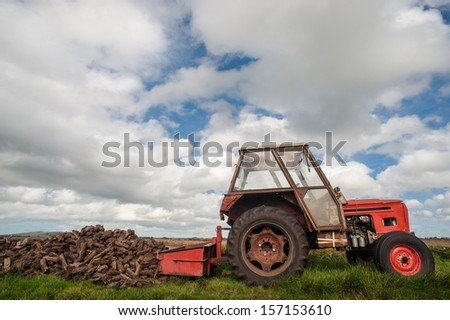 Old tractor collecting bog peat  - stock photo