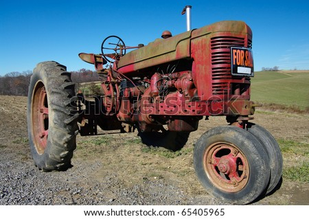 Old Tractor for Sale: An old tractor seeks a new owner. - stock photo