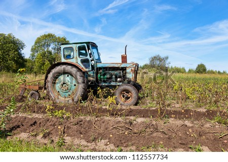 Old tractor in the field - stock photo