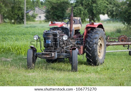 Old tractor on green grass - stock photo