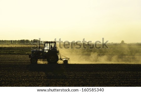 Old tractor plowing - stock photo