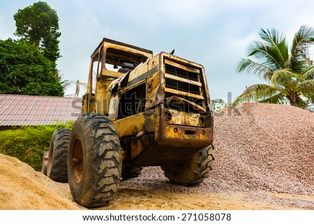 Old tractor pretty near the pile of sand - stock photo