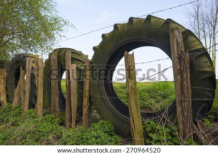 Old tractor tires in a row against the fence of a meadow - stock photo