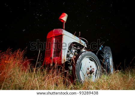 Old tractor under a clear starry night sky. - stock photo