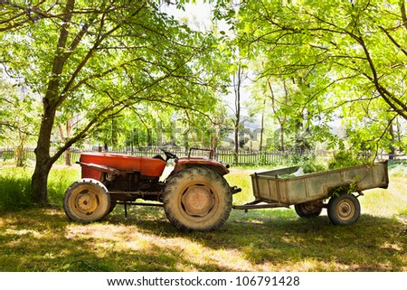 Old tractor with trailer near the trees