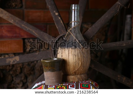 Old traditional bottle of Moldovan homemade wine with clay cup and old wheels in the background