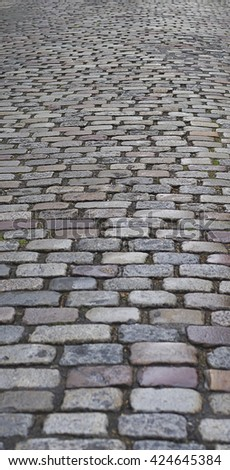 Old  traditional european style long narrow  cobblestone road background with granite blocks, stones and brickwork pattern - stock photo