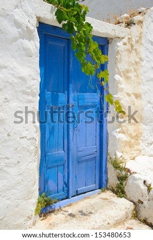 Old traditional greek blue door in white washed cycladic house